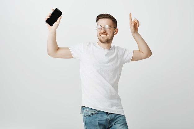 Optymistyczny przystojny facet w okularach tańczy do muzyki w bezprzewodowych słuchawkach z telefonem komórkowym w dłoni