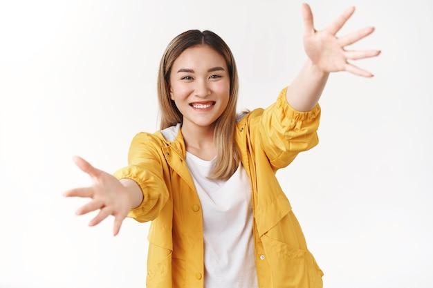 Optymistyczny żywy ładny azjatycki blond dziewczyna sięgnąć rąk do przodu rozciągnąć ramiona aparatu przytulić przytulić chce trzymać pożądany produkt uśmiechnięty rozbawiony szczęśliwie biała ściana