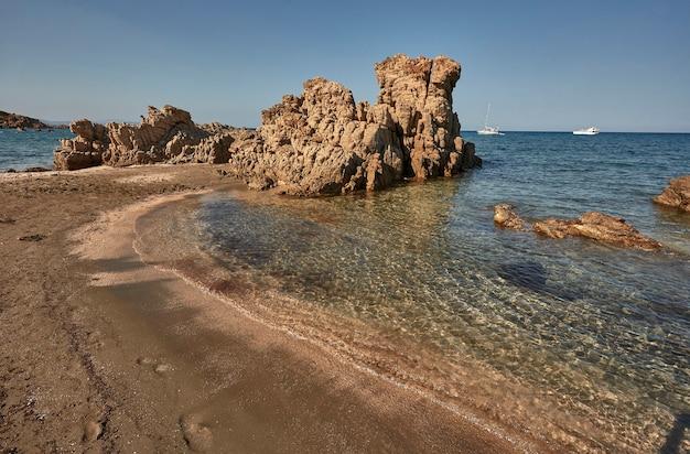 Opustoszała kamienista mała plaża południowej sardynii podczas sierpniowego letniego popołudnia