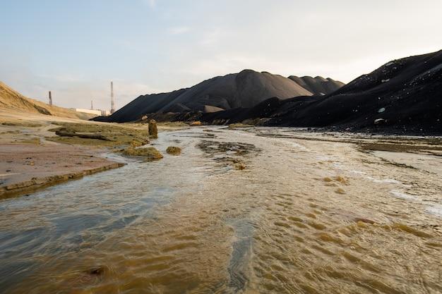 Opustoszałe terytorium z brudną wodą w rzece i zanieczyszczoną glebą otoczone wzgórzami i górami z pochmurnym niebem powyżej i nikim w pobliżu