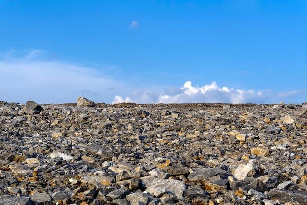 Opustoszały płaski żwirowo-kamienisty teren pod niebem