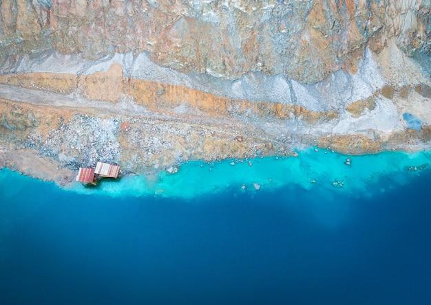 Opuszczona odkrywkowa kopalnia miedzi na górze alesto na cyprze. abstrakcyjna powierzchnia z niebieskim jeziorem, kolorowymi skałami i zardzewiałymi strukturami kopalni. widok z lotu ptaka bezpośrednio nad
