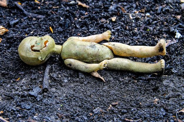 Opuszczona stara zepsuta lalka na szarym jesionowym tle