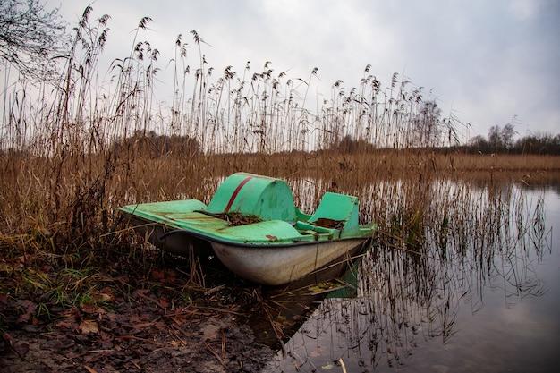 Opuszczona zardzewiała łódź wiosłowa w pobliżu jeziora na brudnym terenie