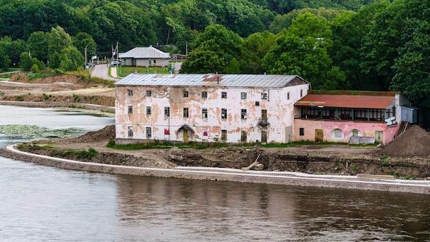Opuszczone budynki mieszkalne nad brzegiem rzeki na granicy rosyjsko-estońskiej.