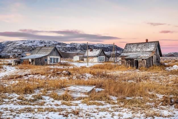 Opuszczone domy na tle arktycznego nieba. stara autentyczna wieś teriberka. półwysep kolski. rosja.