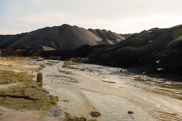 Opuszczone Terytorium Bezużyteczne Z Brudną Wodą W Rzece I Zanieczyszczoną Glebą Otoczone Wzgórzami I Górami, Na Których Nikogo Nie Ma W Pobliżu Premium Zdjęcia