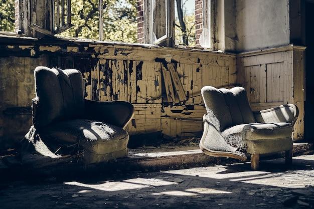 Opuszczony dom z dwoma wysłużonymi kanapami i wybitymi oknami w ciągu dnia