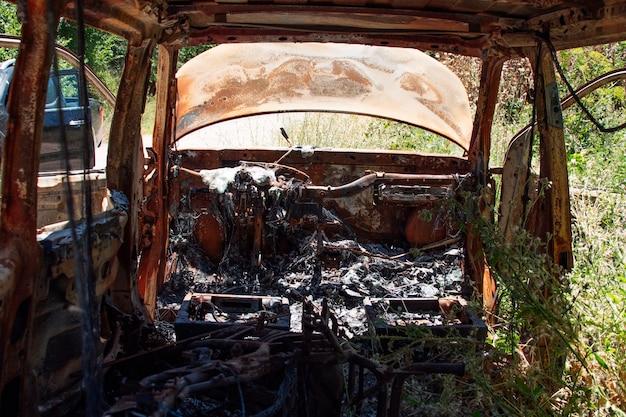 Opuszczony i spalony samochód w środku lasu