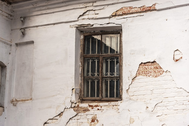 Opuszczony lub zaniedbany dom z uszkodzonymi brudnymi ścianami z cegły i szybą. zwietrzałe mieszkanie na wsi lub w biednym kraju. brudny wygląd zewnętrzny opuszczonego starego budynku w wiosce lub mieście