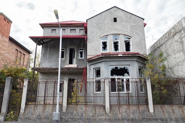 Opuszczony piętrowy dom z wybitymi oknami za wysokim płotem kratowym.