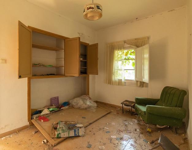 Opuszczony salon z meblami i fotelem