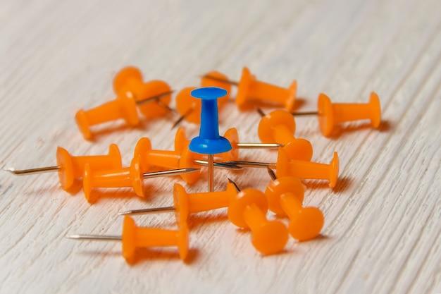 Orange and blue pushpins heap na białym drewnie