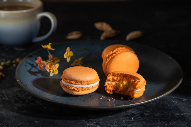 Orange macarons lub macaroons ciasta z filiżanką kawy