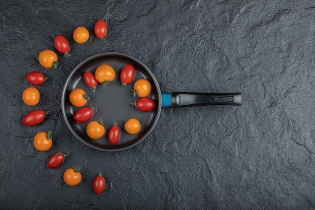Orcanic kolorowe pomidory czereśniowe na patelni na czarnym tle. wysokiej jakości zdjęcie