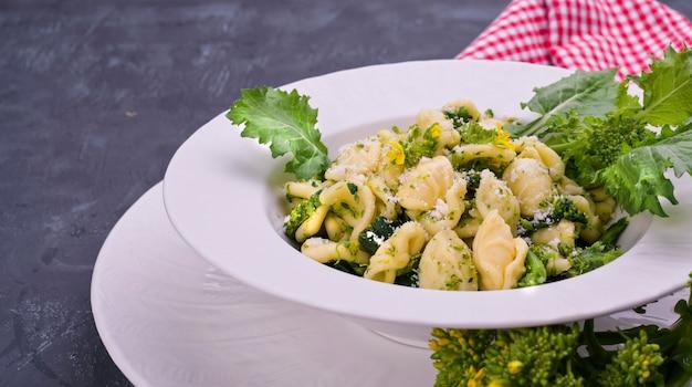 Orecchiette alla pugliese, domowy włoski makaron. orecchiette z wierzchołkami rzepy. tradycyjne jedzenie z południa włoch, na białym tle. skopiuj miejsce