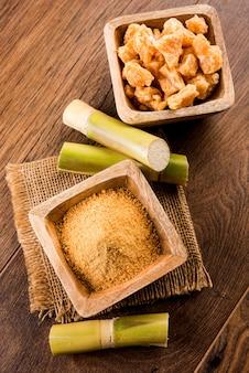 Organic gur lub jaggery powder to nierafinowany cukier otrzymywany z zagęszczonego soku z trzciny cukrowej. podawane w misce. selektywne skupienie