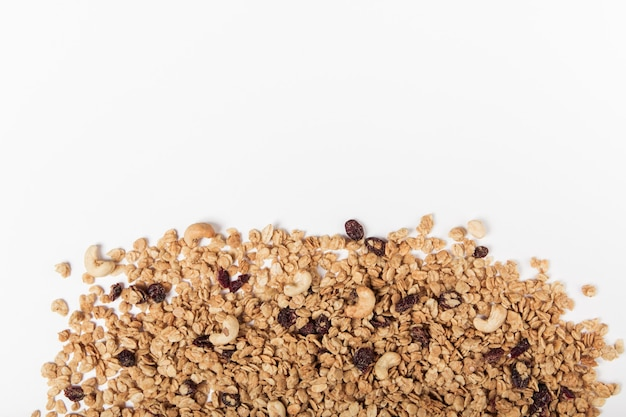 Organiczna granola z orzechami, żurawiną i rodzynkami na białym tle.