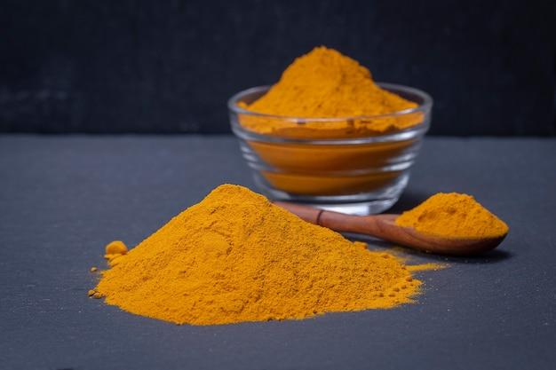 Organiczna kurkuma, kurkuma w proszku na czarnym tle półmisek łupków. curry w proszku. ścieśniać