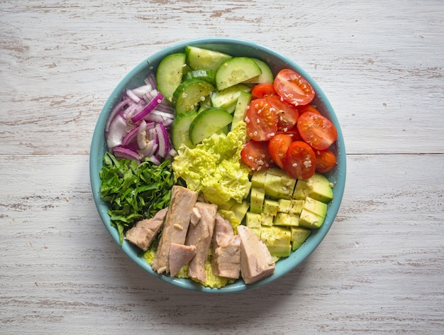 Organiczna sałatka jarzynowa z plasterkami tuńczyka na talerzu. widok z góry.