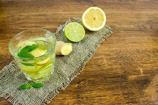 Organiczna soda imbirowa w szklance z cytryną i limonką
