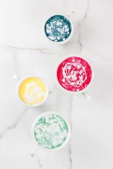 Organiczna wegańska kawa latte, bezkofeinowa kurkuma, buraki, wodorosty i matcha. na białym marmurowym tle, widok z góry copyspace