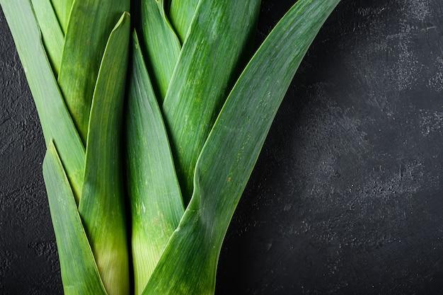 Organiczna zielona cebula porowa na czarnym stole z teksturą, widok z góry