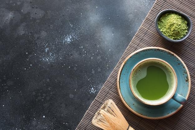 Organiczna zielona herbata matcha na czarnym stole.