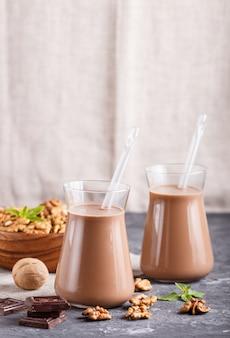 Organiczne bez mlecznego mleka czekoladowego z orzecha włoskiego w szklanym i drewnianym talerzu z orzechami na czarnym tle betonu.