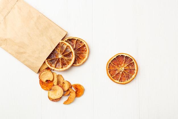 Organiczne chipsy z suchych owoców w papierowym ekologicznym opakowaniu na białym tle