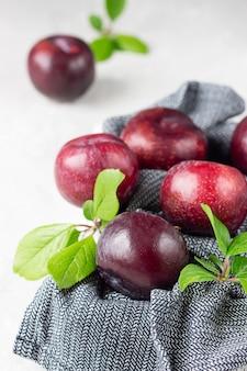 Organiczne fioletowe śliwki z liśćmi
