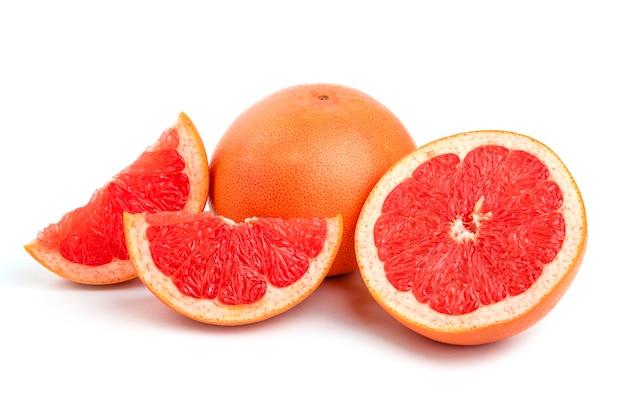 Organiczne grejpfruty na białym tle, całe lub w plasterkach.