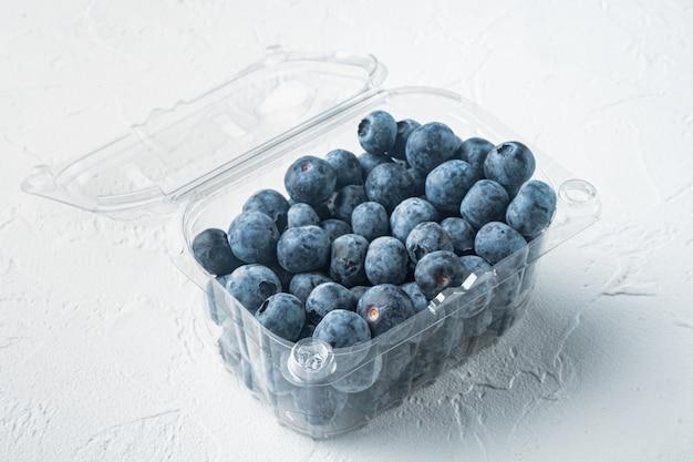 Organiczne jagody w plastikowym pudełku na białym tle