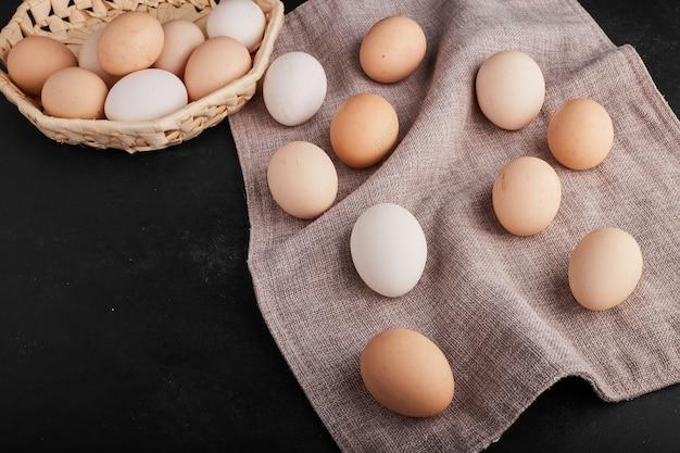 Organiczne jajka na ręczniku kuchennym iw bambusowym kubku.
