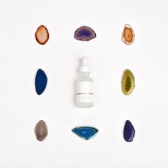 Organiczne kosmetyki apteczne z naturalnym agatem na białym tle. leżał na płasko. widok z góry na butelkę kremu. naturalne kosmetyki do brandingu makiety. kompozycja kamieni naturalnych.