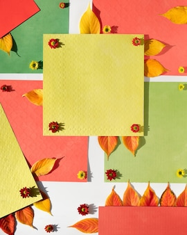 Organiczne kształty papieru z jesiennymi żółtymi liśćmi i małymi kwiatami chryzantem.