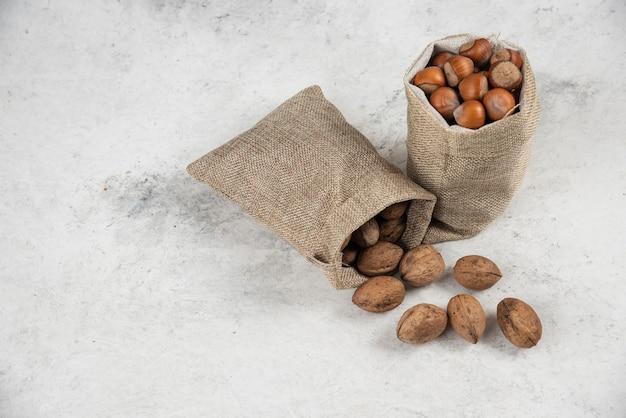 Organiczne łuskane orzechy laskowe i orzechy włoskie w worze na marmurowym stole.