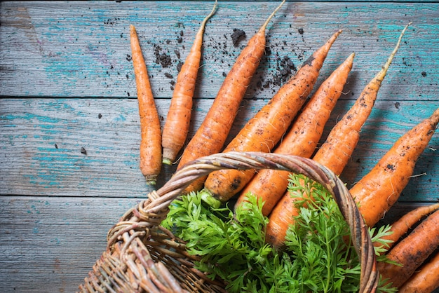 Organiczne marchewki w wattled koszykowym odgórnym widoku drewnianym