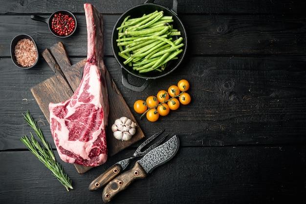 Organiczne, marmurkowe mięso wołowe zestaw do steków i przypraw, krojony tomahawk, na drewnianej desce do krojenia, na czarnym drewnianym stole
