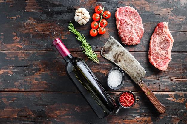 Organiczne mięso cięte z górnym ostrzem, surowy, marmurkowy stek wołowy, ze starym tasakiem do noża rzeźniczego, butelką czerwonego wina i przyprawami na ciemnym drewnianym stole rustykalnym, widok z góry z miejscem na tekst.