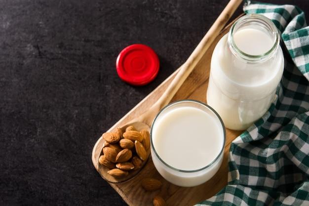 Organiczne mleko migdałowe w szkle i butelce na czarno. widok z góry