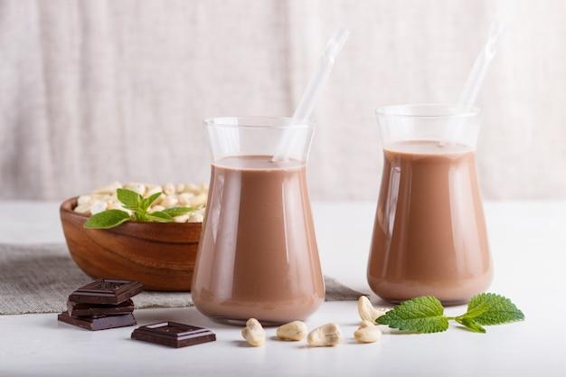 Organiczne mleko mleczne nerkowca w szklanym i drewnianym talerzu z orzechami nerkowca na szarym betonie.