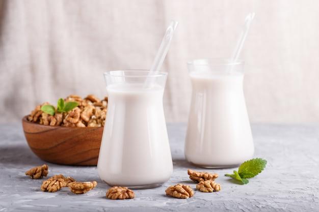 Organiczne mleko mleczne orzechowe w szkle i drewniana płyta z orzechami na szarym betonie.