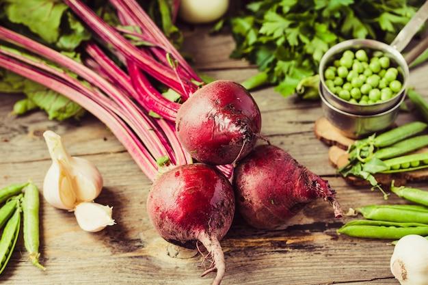 Organiczne młode buraki, warzywa, czosnek na drewnianym stole. jesienne świeże warzywa. selektywne skupienie.