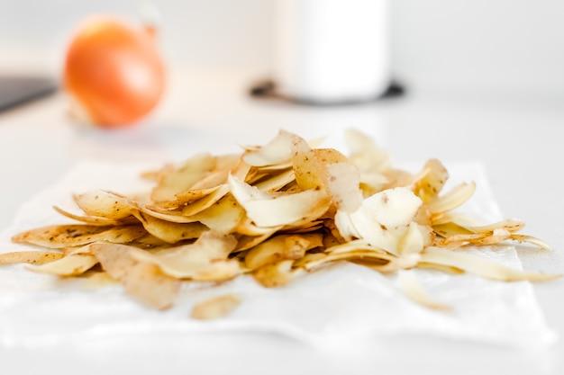 Organiczne odpady żywnościowe z domowej kuchni gotowe do kompostowania. koncepcja ekologiczna. resztki jedzenia, obierki warzywne na kuchennym stole. zachowanie ekologiczne, zarządzanie odpadami, recykling śmieci.