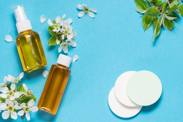 Organiczne oleje kosmetyczne i gąbki na niebieskim tle z białymi wiosennymi kwiatami.