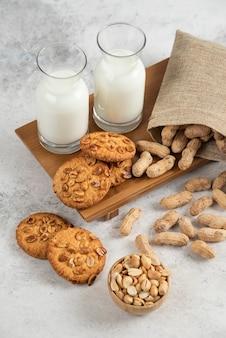Organiczne orzeszki ziemne, świeże mleko i pyszne ciasteczka na marmurowym stole.