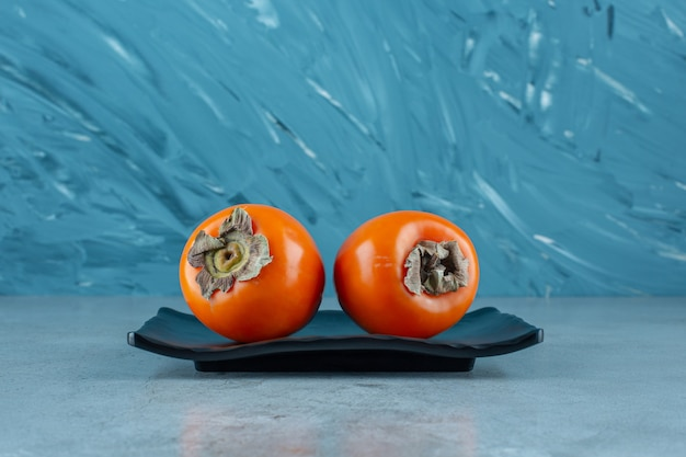 Organiczne persymony na czarnym talerzu, na marmurowym stole.
