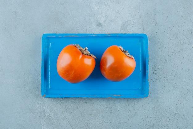 Organiczne persymony na niebieskim drewnianym talerzu, na marmurowym tle. zdjęcie wysokiej jakości