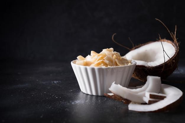 Organiczne płatki kokosowe z cukrem i solą w białej misce na czarno
